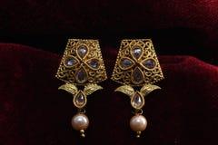L'or a plaqué des bijoux - macro image de boucles d'oreille d'or de fantaisie de concepteur photographie stock libre de droits