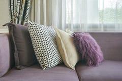 L purpurfärgad soffa för form med stilfulla kuddar i vardagsrum fotografering för bildbyråer