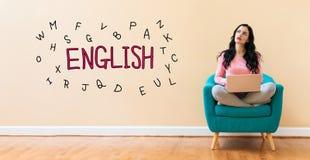 L?ra engelskt tema med kvinnan som anv?nder en b?rbar dator fotografering för bildbyråer