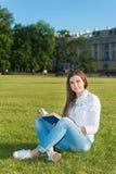 l'Ragazza-allievo si siede su prato inglese e legge il manuale Immagine Stock Libera da Diritti