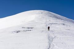 l'Sci-alpinista va in salita sciare su un picco di montagna Fotografia Stock