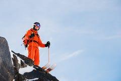 L'sciatore-atleta professionista sta sull'orlo di alta scogliera contro un cielo blu un giorno soleggiato Fotografia Stock