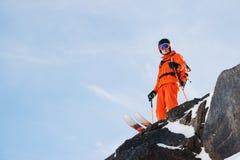 L'sciatore-atleta professionista sta sull'orlo di alta scogliera contro un cielo blu un giorno soleggiato Fotografia Stock Libera da Diritti