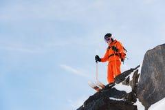 L'sciatore-atleta professionista sta sull'orlo di alta scogliera contro un cielo blu un giorno soleggiato Immagine Stock