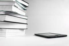 L?seb?cker med en EBook Bunt av böcker och eBook på vit bakgrund royaltyfri foto