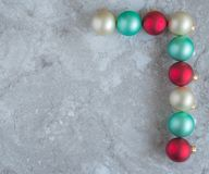 L shaped border of colorful round Christmas ornaments. Reverse L shaped border of colorful round Christmas ornaments on a gray marble counter top with copy space royalty free stock photography