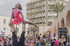 Öl-Sheva ISRAEL - mars 5, 2015: Flicka och man - gymnaster utför för åhörarna på den öppna etappen - Purim Arkivfoto