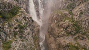 4l - Tir aérien au-dessus d'une haute cascade parmi les roches en pierre dans le Caucase banque de vidéos