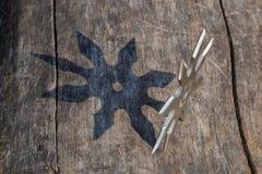 L'?toile de lancement de Shuriken, arme froide de ninja japonais traditionnel a coll? ? l'arri?re-plan en bois photo libre de droits