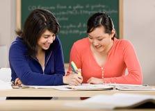 L'étudiant avec des manuels aidant l'ami font le travail Images stock