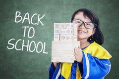 L'étudiant d'école primaire tient des blocs de lettre Photographie stock