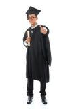 L'étudiant masculin asiatique dans la robe d'obtention du diplôme manient maladroitement  Image stock