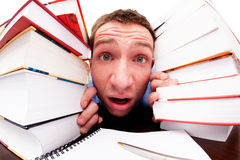 L'étudiant regarde par derrière les livres Photographie stock