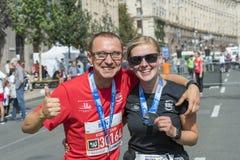 L'Ucraina, Kiev, Ucraina 09 09 2018 una coppia felice dei corridori dopo una maratona Corridori deboli di mente felici dopo avere fotografia stock