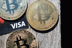 L'Ucraina, Kremenchug - marzo 2019: Bitcoins dorato sulla carta di visto e sul fondo di legno immagini stock