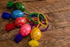 L'ucranino ha colorato le uova di Pasqua con gli ornamenti su un fondo di legno immagini stock