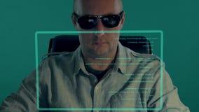 L'ufficiale bianco calvo si siede davanti allo schermo virtuale ed al codice di battitura a macchina di programma L'uomo in vetri archivi video