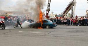 L'ufficiale del fuoco con un estintore mette fuori il fuoco che arde dall'automobile stock footage