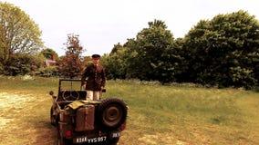 L'ufficiale di esercito bello di GI dell'americano WWII in uniforme sta sulla jeep di Willy e saluta archivi video