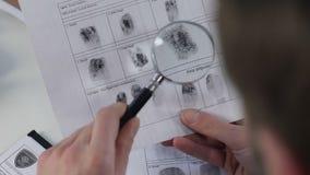 L'ufficiale di polizia che controlla le impronte digitali archiva con la lente d'ingrandimento, l'identificazione stock footage