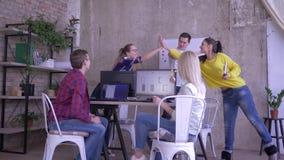 L'ufficio moderno di affari, giovani lavoratori creativi accoglie favorevolmente il nuovo impiegato e darsi alti cinque archivi video