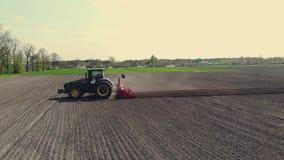 L'UKRAINE, CHERKASY, LE 5 MAI 2019 : levé aérien, grand tracteur avec des tours spéciaux d'équipement par le champ labouré du noi banque de vidéos