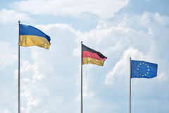 L'Ukrainien, les drapeaux allemands et le drapeau de l'Union européenne dans la perspective des nuages Photos libres de droits