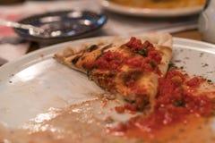 L'ultimo pezzo di pizza di Calzone su un piatto bianco Immagini Stock Libere da Diritti