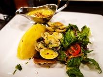 L'un pezzo solo del salmone scottato pentola su un piatto bianco con le foglie della lattuga è servito con la salsa di tartaro Immagine Stock