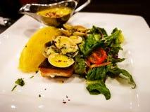 L'un pezzo solo del salmone scottato pentola su un piatto bianco con le foglie della lattuga è servito con la salsa di tartaro Fotografia Stock Libera da Diritti