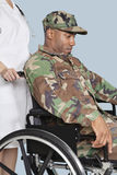 L'uniforme de port de camouflage de soldat triste des USA Marine Corps dans le fauteuil roulant a aidé par l'infirmière féminine Photographie stock libre de droits