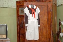 L'uniforme scolastico sovietico anteriore con un legame aprente la strada che appende sopra Immagini Stock