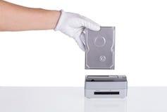 L'unité de disque dur dans sa main est reliée à la station d'accueil Photos libres de droits
