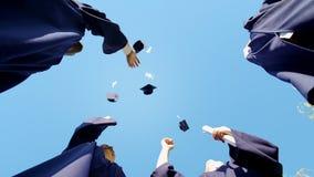 L'université reçoit un diplôme le lancement vers le haut de leur tradition d'étudiant de chapeaux carrés, vue inférieure images libres de droits