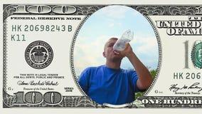 L'uomo è acqua potabile nel telaio della banconota in dollari 100 stock footage
