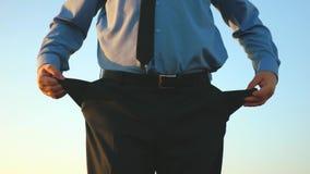 L'uomo è fallimento Affare del mendicante Impresa rovinata Uomo in tasche vuote di torsioni del legame di debito contro cielo blu video d archivio