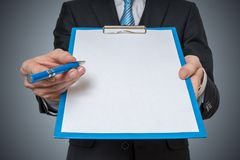 L'uomo è mostrante ed offrente il Libro Bianco in bianco in lavagna per appunti con la penna immagini stock