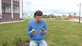 L'uomo è scrivere messaggi su due telefoni cellulari video d archivio