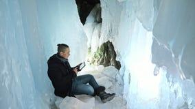 L'uomo è si siede su Internet in compressa in una caverna di ghiaccio Intorno alla bella grotta misteriosa del ghiaccio L'utente  stock footage