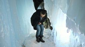 L'uomo è si siede su Internet in compressa in una caverna di ghiaccio Intorno alla bella grotta misteriosa del ghiaccio L'utente  archivi video