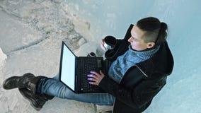 L'uomo è si siede su Internet in computer portatile in una caverna di ghiaccio Intorno alla bella grotta misteriosa del ghiaccio  video d archivio