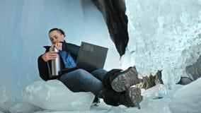 L'uomo è si siede su Internet in computer portatile in una caverna di ghiaccio Intorno alla bella grotta misteriosa del ghiaccio  stock footage
