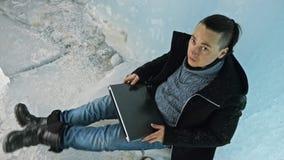 L'uomo è si siede su Internet in computer portatile in una caverna di ghiaccio Intorno alla bella grotta misteriosa del ghiaccio  archivi video