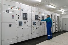 L'uomo è sottostazione interna di distribuzione di energia elettrica Fotografie Stock Libere da Diritti