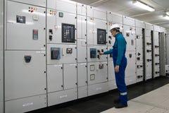 L'uomo è sottostazione interna di distribuzione di energia elettrica Immagine Stock