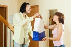 L'uomo è venuto ad una buona donna con un regalo a casa Fotografie Stock