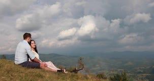 L'uomo abbraccia la bella offerta della donna mentre si siedono da un fuoco di accampamento prima di un Mountain View splendido archivi video