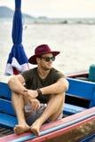 L'uomo abbronzato con stoppia sta navigando sulla barca variopinta immagine stock libera da diritti
