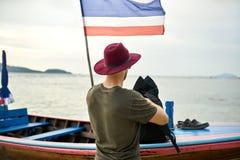 L'uomo abbronzato con stoppia sta tenendo il suo zaino vicino alla barca di legno immagini stock libere da diritti
