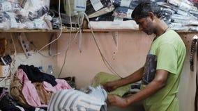 L'uomo abbronzato riveste di ferro la camicia con ferro da stiro nell'officina della via stock footage